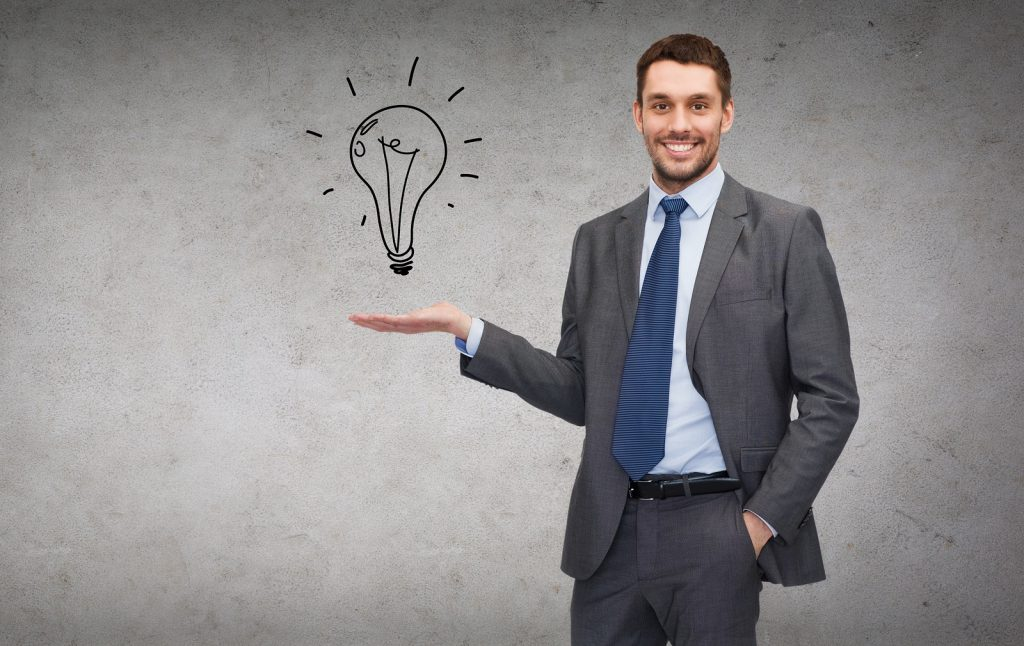 business, office, advertising and people concept - friendly young buisnessman showing light bulb on
